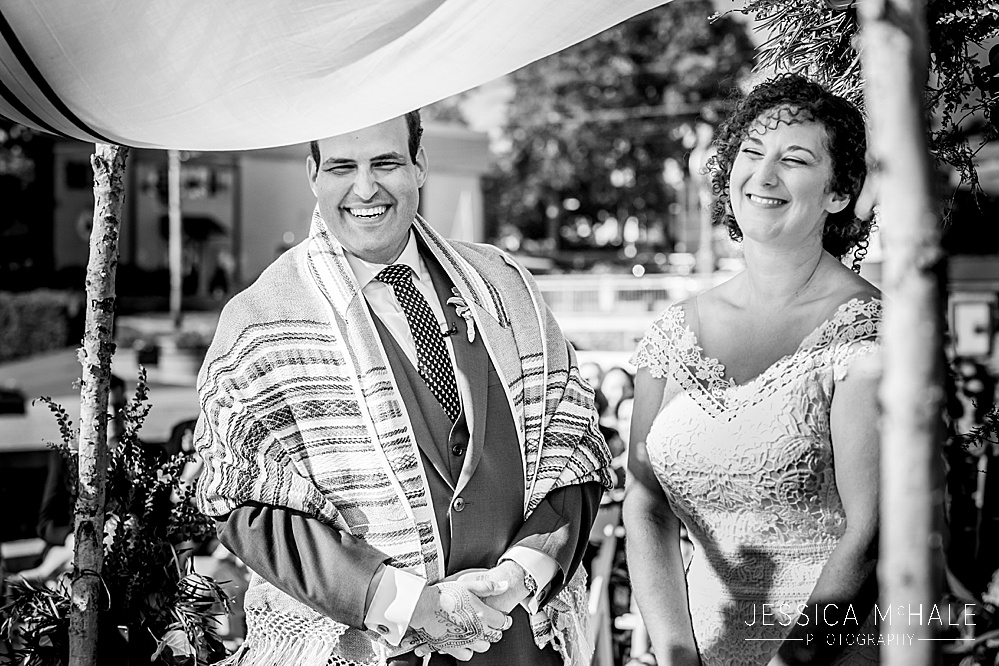 Jewish bride and groom smiling during there ceremony at their Herreshoff Maritime Museum Wedding
