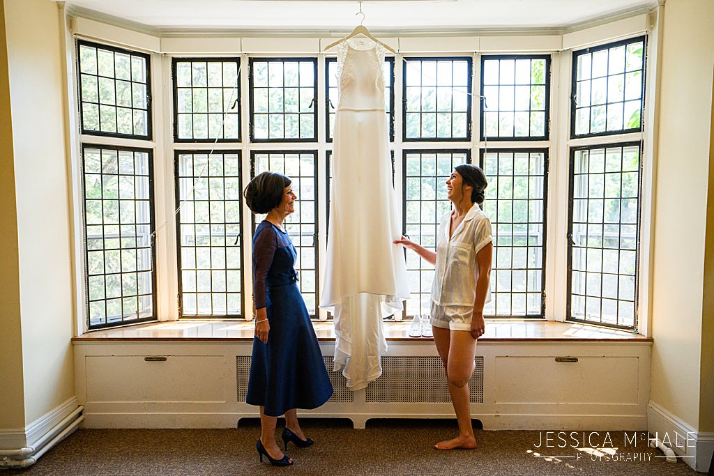 mother and bride looking at wedding dress in front of windows
