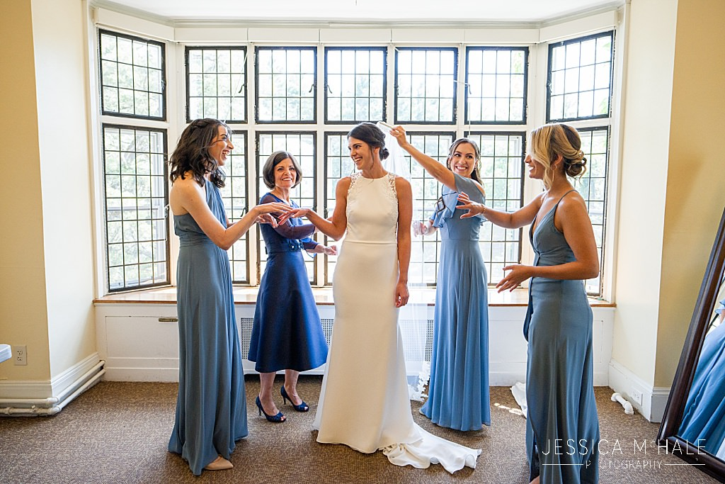 bridesmaids with bride in front of windows