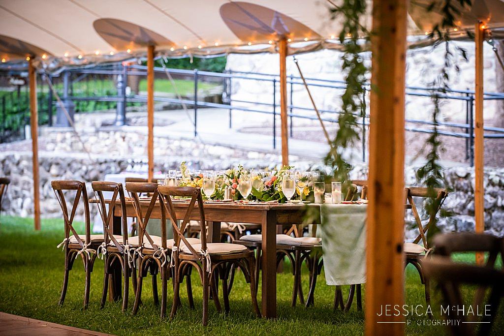 farmhouse table under sailcloth tent at wedding reception